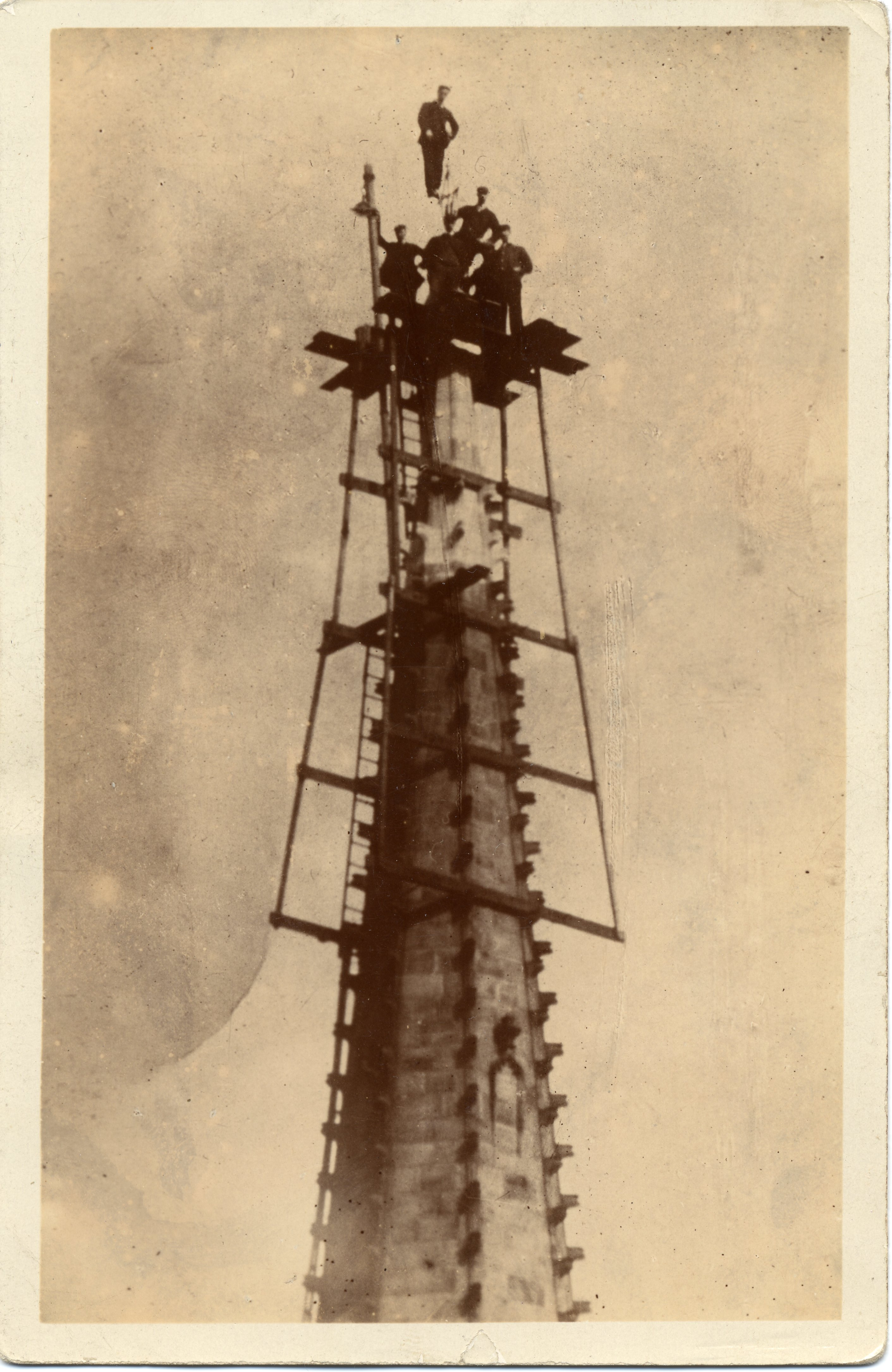 A postcard of men working on Wakefield Cathedral spire
